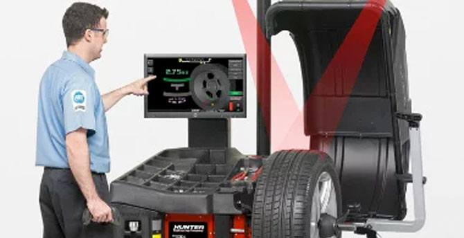 mechanic using smartweight touch system to balance tires